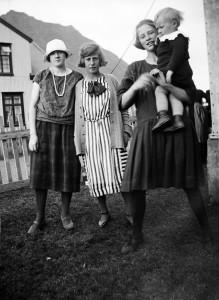 1915-1925, þrjár ungar konur og lítið barn standa í húsagarði, sennilega á Ísafirði.