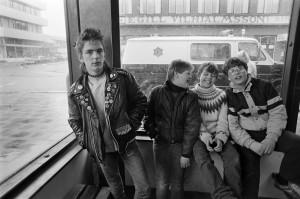 19. apríl 1983, unglingar á Hlemmi. Til vinstri er drengur í leðurjakka, kallaður Siggi. Til hægri eru yngri drengir. Fyrir utan er lögreglubifreið, Svarta maría. Helgarpósturinn, 22. apríl 1983.